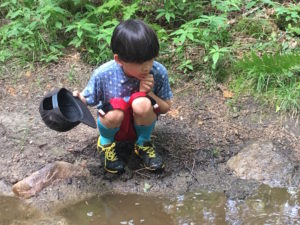 8 year old boy squats by a puddle, looking for frogs